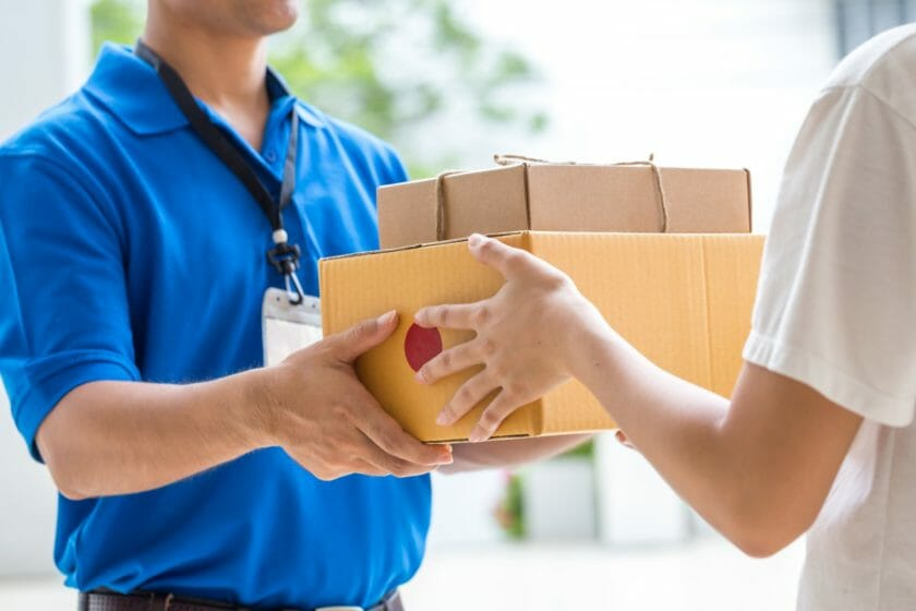 courier handing parcels to customer