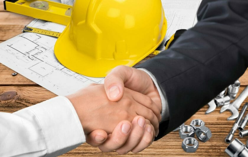 contractors shaking hands in front of desk with hard hat and plans