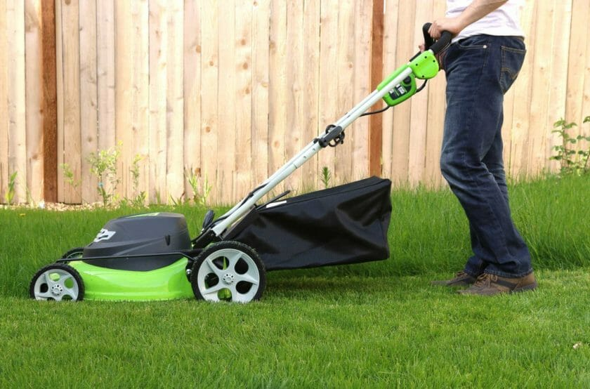 gardener mowing a very green lawn