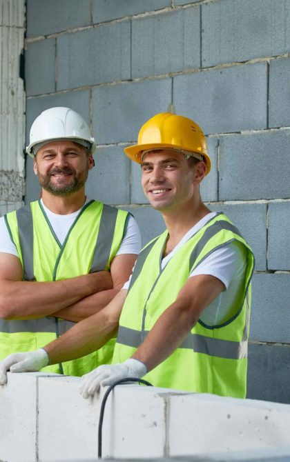 2 builders smiling at the camera at the cost of their builders insurance