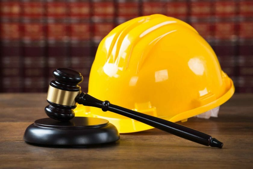 hard hat and gavel in legal courtroom