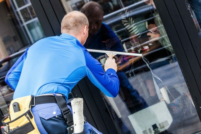 window cleaner wearing a tool belt and cleaning a window