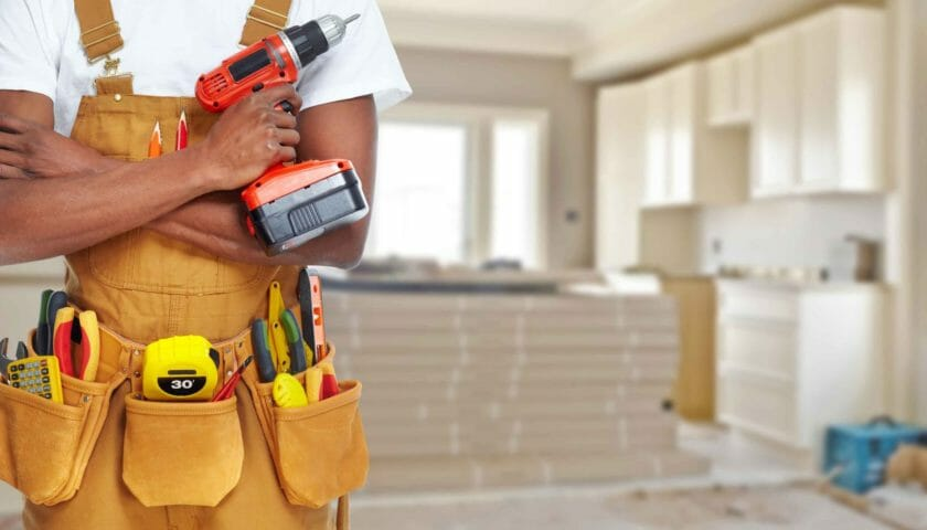 self-employed handyman standing with tool belt and drill thinking about what insurance he needs