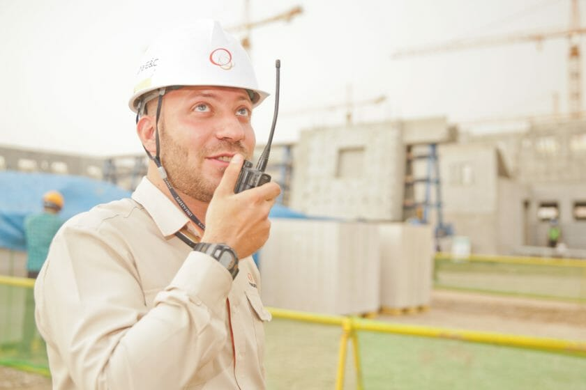 man wearing hard hat holding walkie talkie