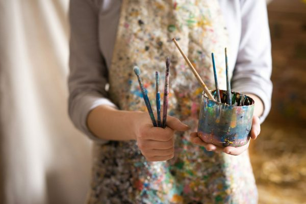 artist holding paint pot and brushes