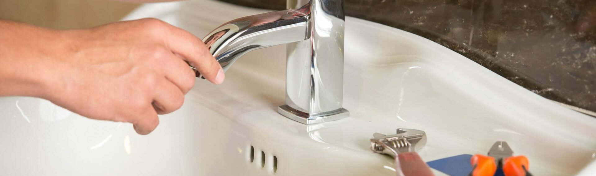 bathroom installer fixing tap on sink