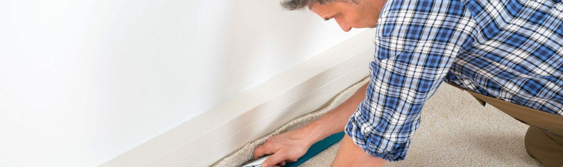 carpet fitter cutting the edge of a cream carpet