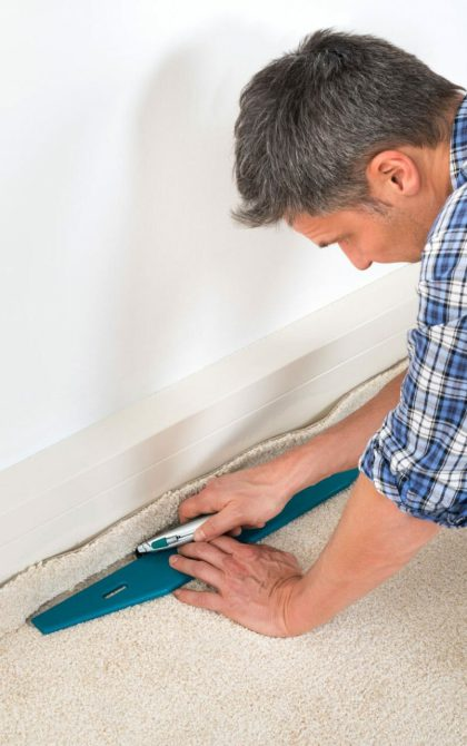 carpet fitter cutting the edge of a cream carpet