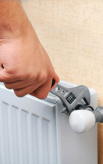 central heating installer working on radiator with spanner