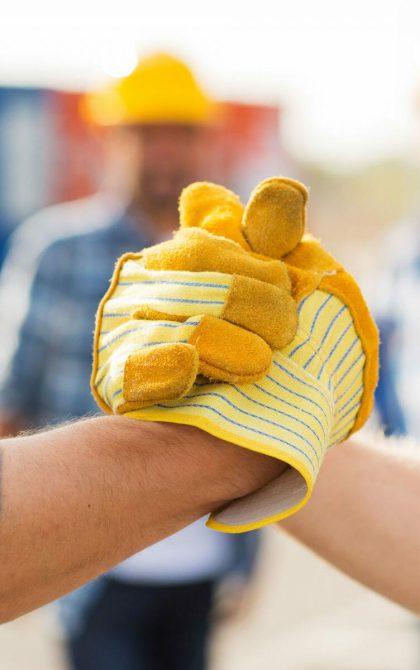 contractors in yellow gloves shaking hands