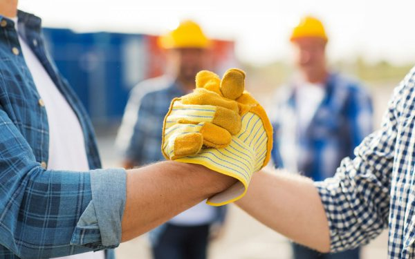 contractors in yellow gloves shaking hands