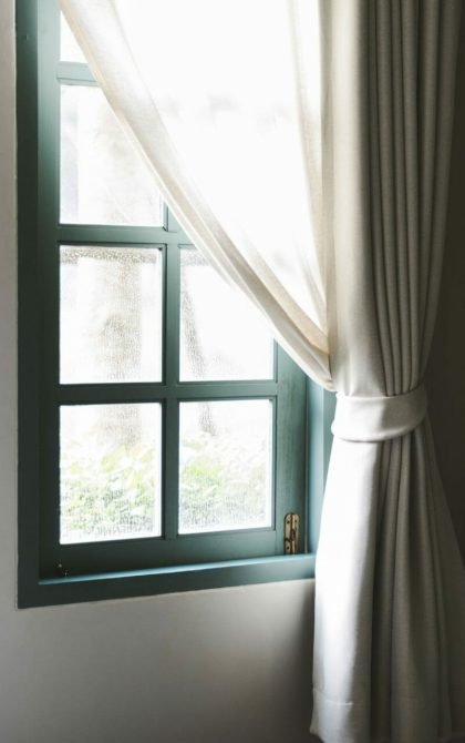 white curtains over a green window