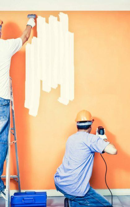 3 tradesman decorating a room with orange paint