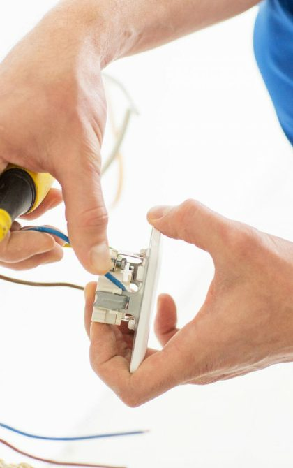 electrician with screwdriver installing electrical socket