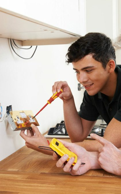 electricians working together to replace a socket
