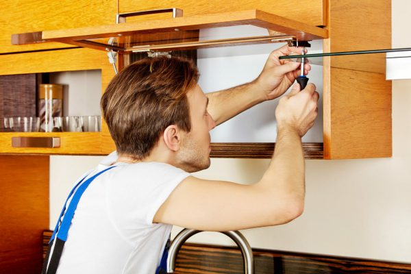 handyman with screwdriver fixing cupboard