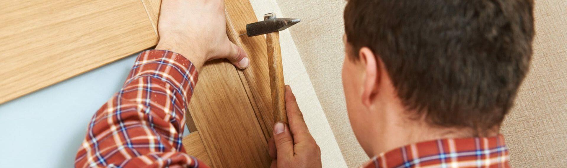 handyman using hammer to repair door