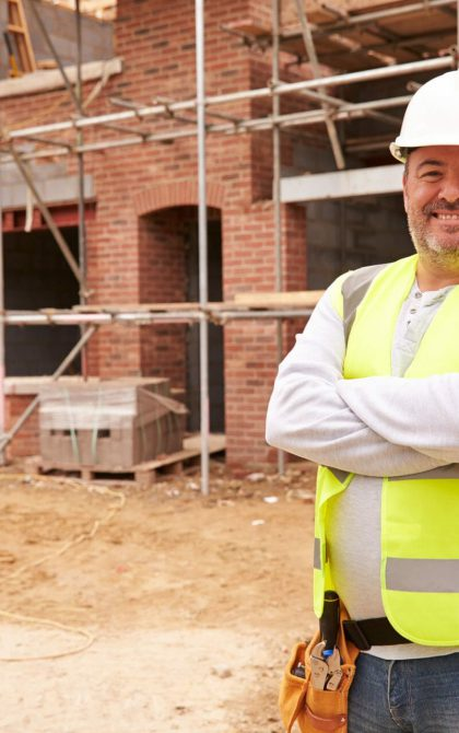 smiling house builder on building site