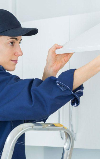 female tradesman fitting kitchen cupboard