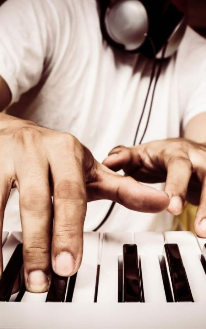 musician with headphones playing a keyboard