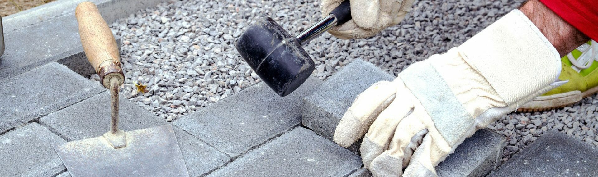 tradesman laying block paving