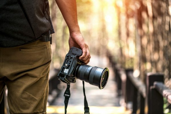 photographer holding large camera with strap by his side