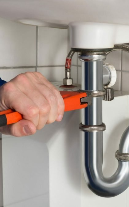 plumber using orange wrench to tighten sink pipe work