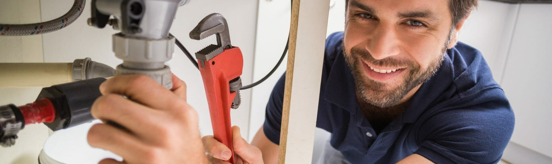 smiling plumber fixing a sink