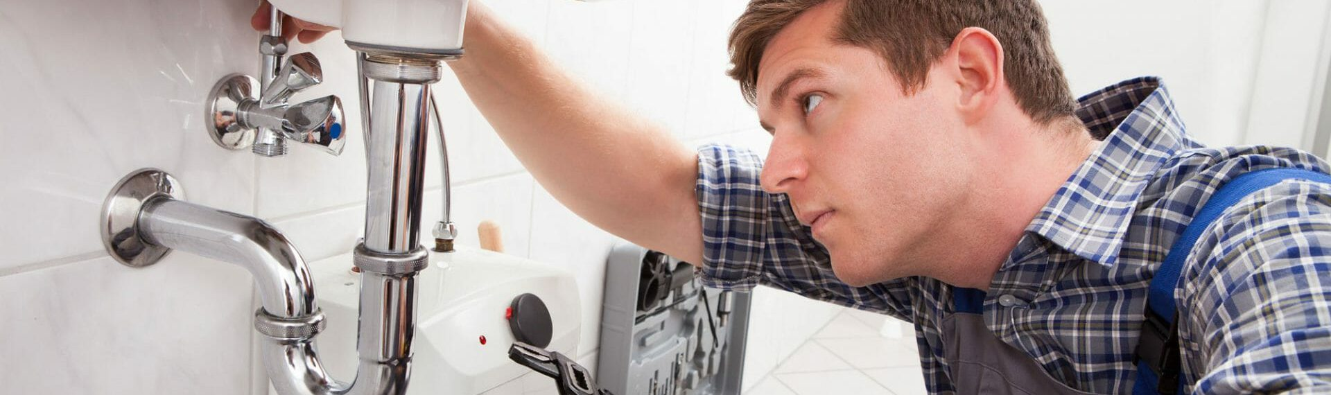 plumbing contractor working on white sink