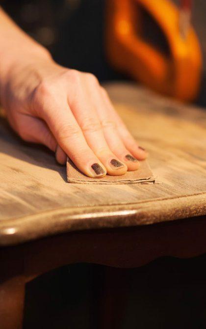 furniture restorer sanding wooden table