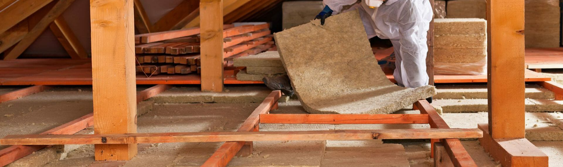 roofer installing insulation in a loft space