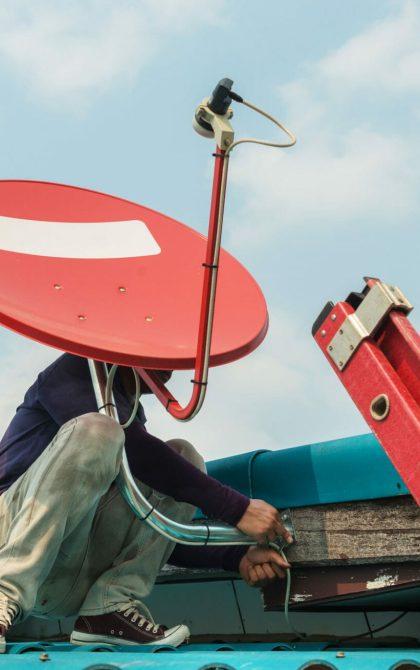 aerial engineer installing satellite dish on roof