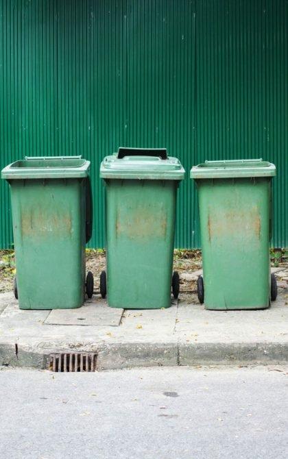 3 green wheelie bins on pavement