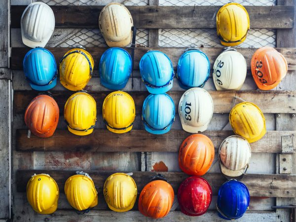 builders coloured hard hats hanging on wall