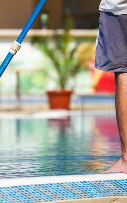 swimming pool cleaner standing on side of pool