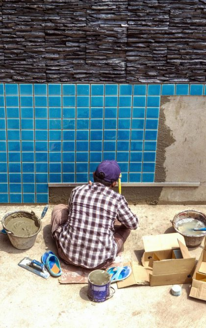 swimming pool contractor tiling the side of a swimming pool