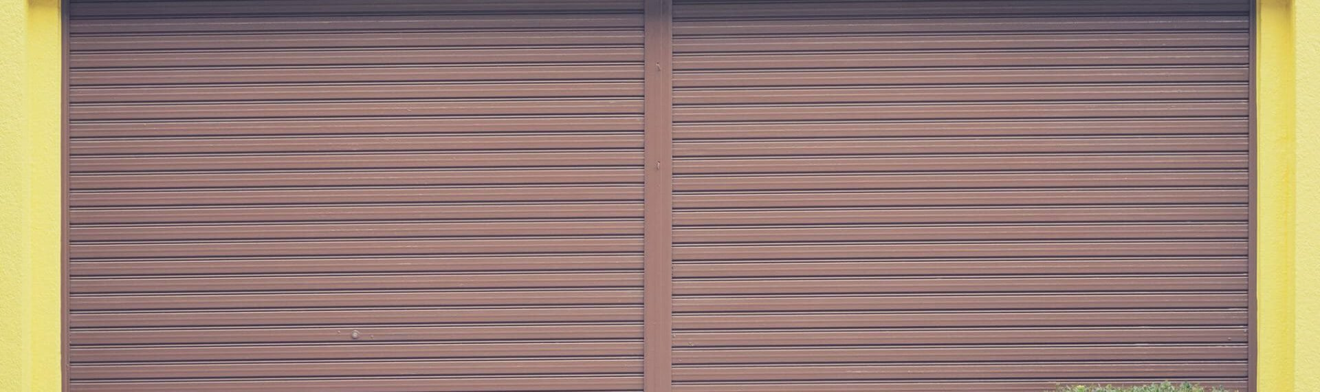 brown roller shutter door installed in a yellow building