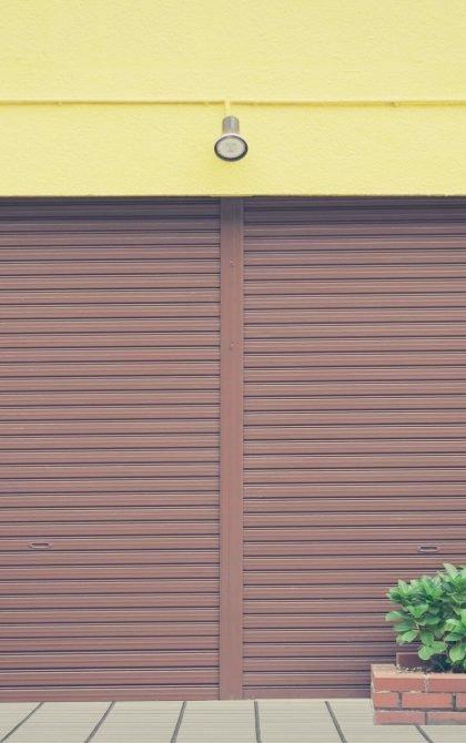 brown roller shutter door installed in a yellow building