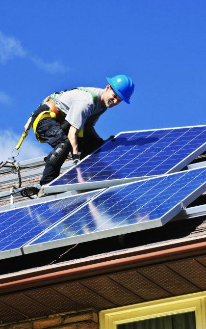 solar panel installer installing solar panels on a roof