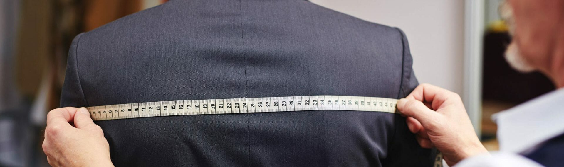 tailor using tape during suit fitting