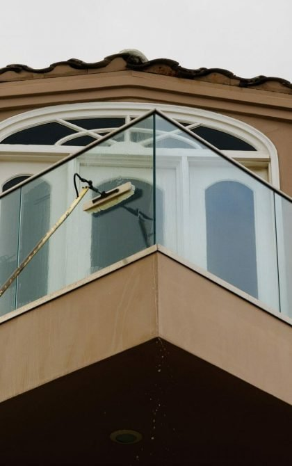window cleaner using water fed pole method to clean a glass balcony